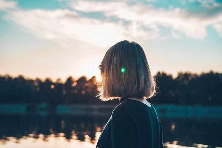 Una mujer de espaldas frente a un lago con árboles de fondo