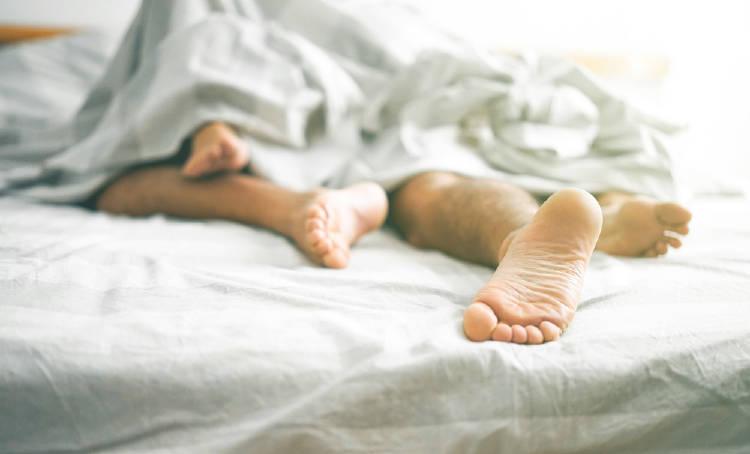 pies pareja cama