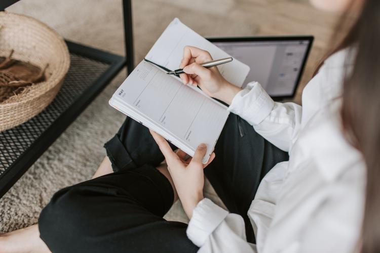 Mujer sentada escribiendo en agenda