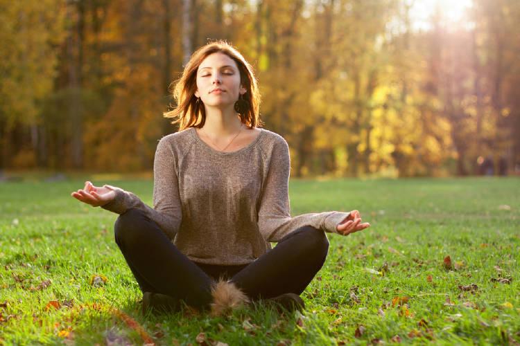 mujer medita en postura de loto en la naturaleza