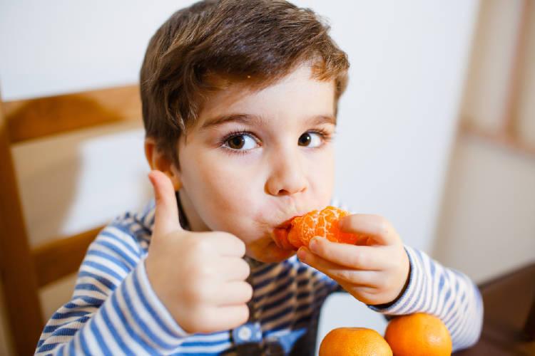 Niño come frutas