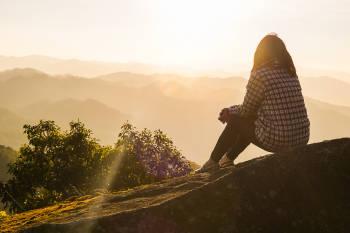 mujer en una montaña al atardecer
