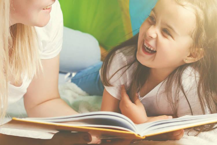 Una niña lee un libro con su madre