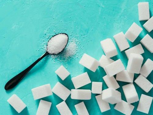 Cubos de azúcar y una cuchara con azúcar en granos sobre un fondo celeste