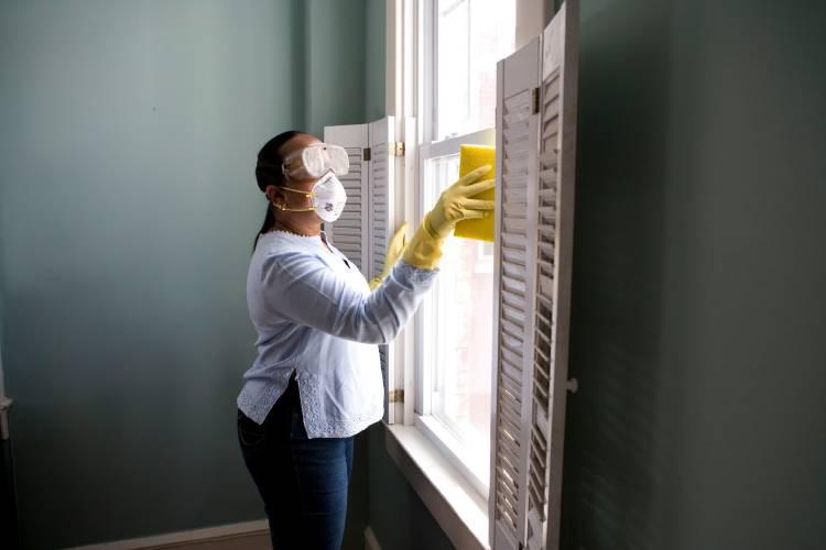 senora limpiando ventanas con guantes, tapabocaa y lente