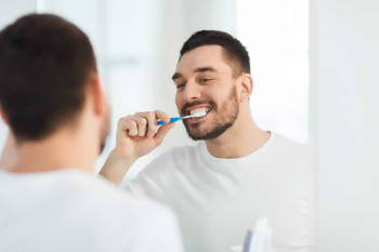 hombre cepilla sus dientes frente al espejo con remera blanca