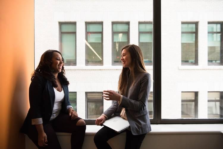 Dos mujeres conversando en una oficina