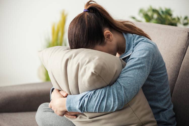 mujer apoya su cabeza contra una almohada en señal de agotamiento
