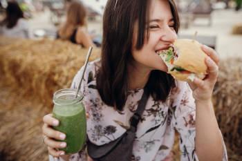 vegana feliz come una hamburguesa y un batido verde