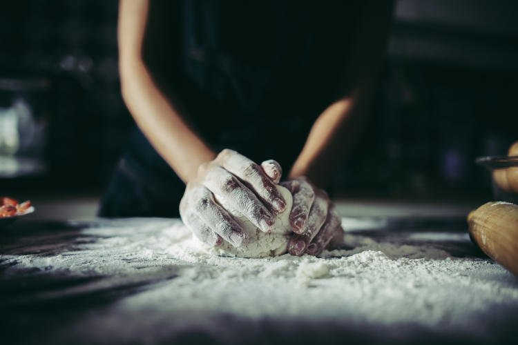 woman-kneads-dough-for-make-pizza-on-wooden-cooking-concept