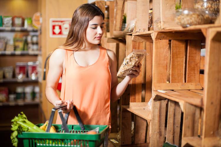 Una mujer mirando las etiquetas de los productos que compra
