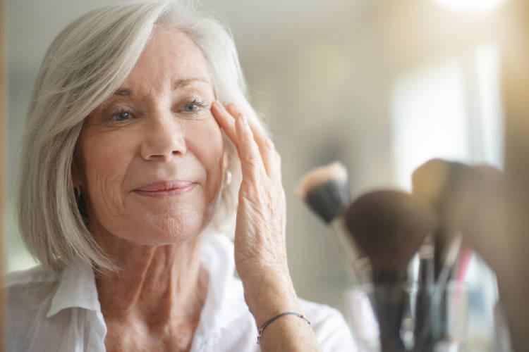 Una mujer con canas se maquilla frente al espejo