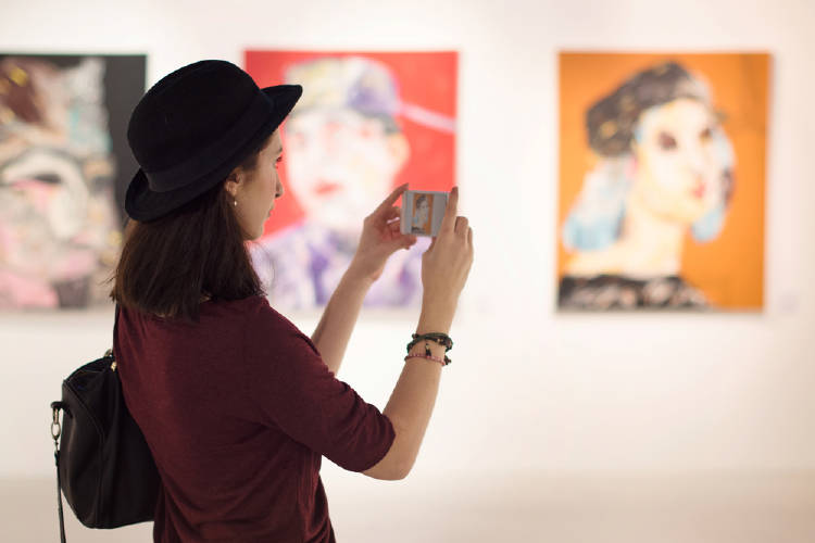 joven observa obras de arte y las captura con su movil en un museo de arte moderno