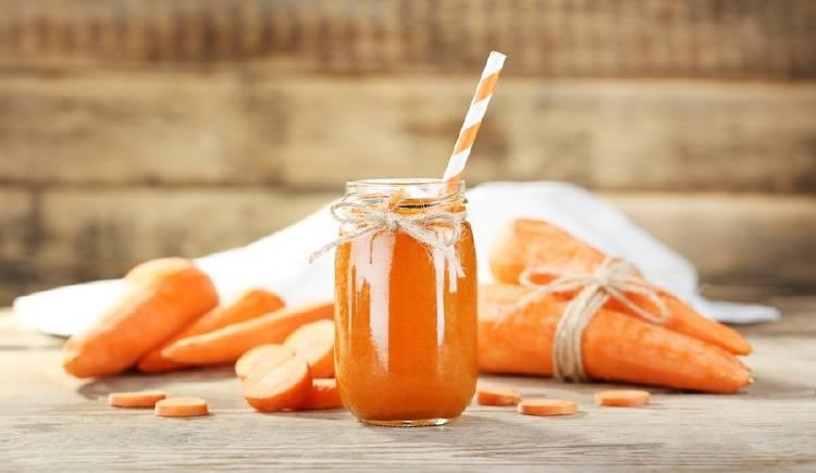 Jugo de zanahora en un frasco, con otras zanahorias alrededor