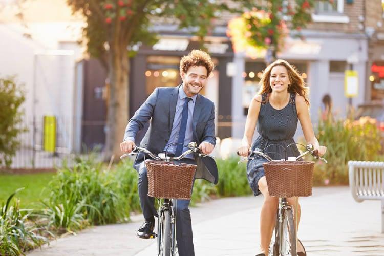 Dos personas andan en bicicleta en la ciudad