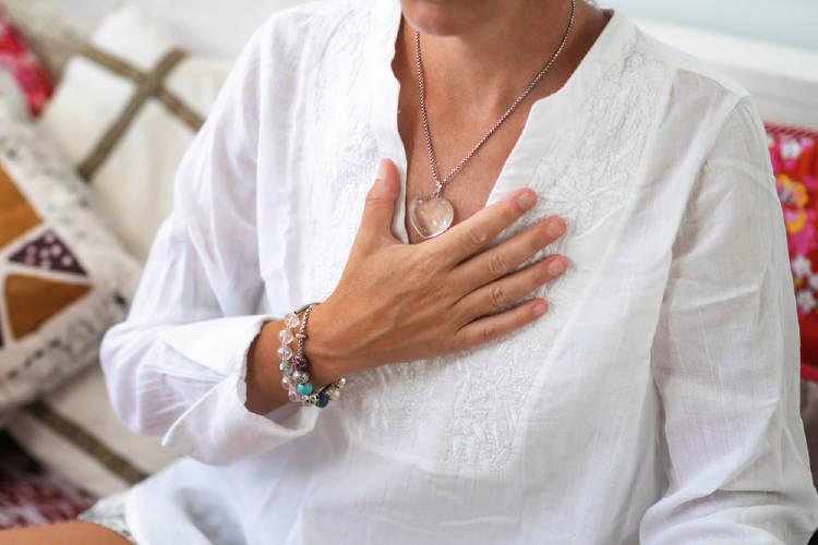 mujer medita con mano en el chakra corazon