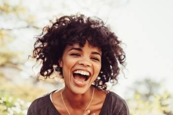 Una mujer riéndose en un día soleado