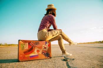 mujer sentada sobre una maleta en la ruta