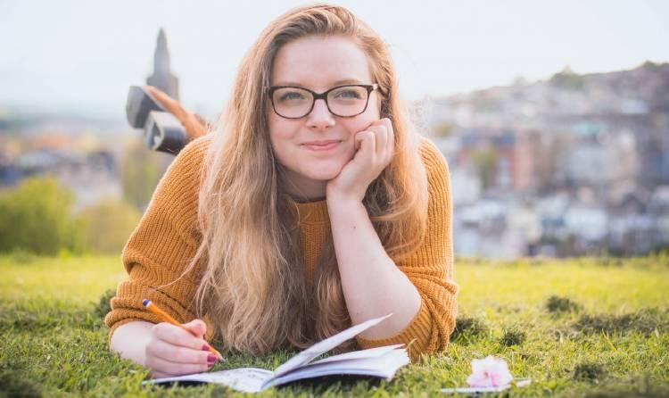 Una mujer escribe en un cuaderno recostada sobre el césped