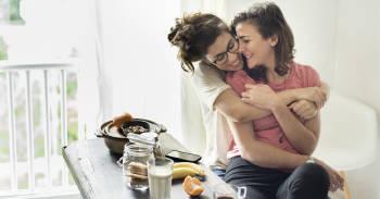 pareja se abraza desayunando