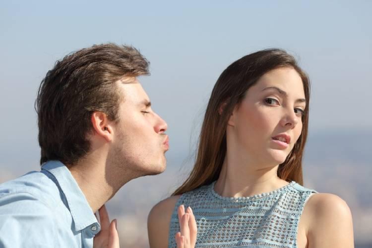 Una mujer rechaza el beso de un hombre