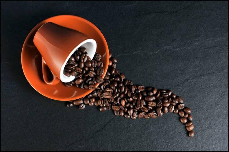 Una taza con granos de café volcada sobre una superficie negra