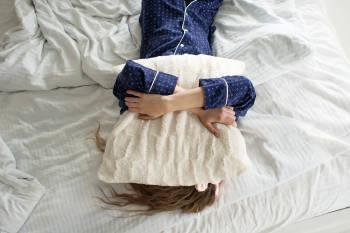 Una mujer en la cama con una almohada sobre la cara