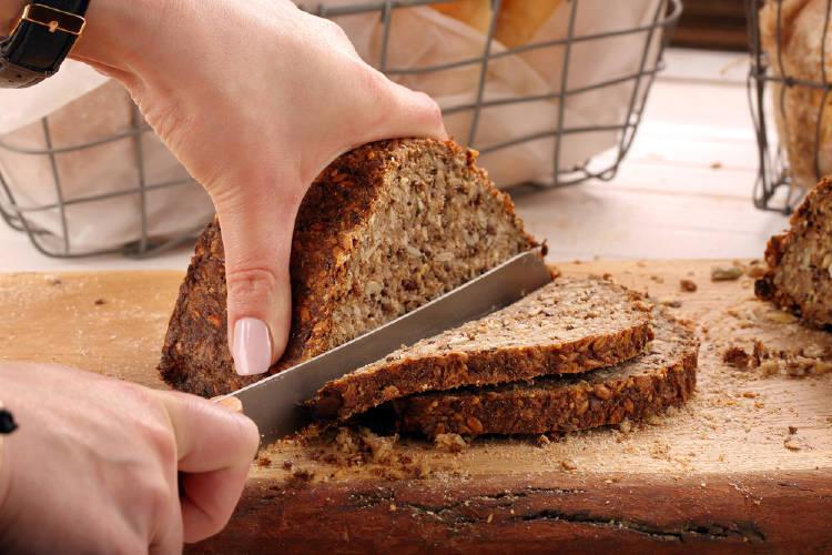 mujer cortando un pan integral