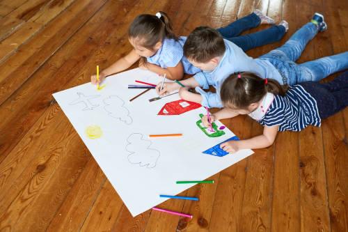 tres niños pequeños dibujan con colores sobre el un papel blanco en el suelo