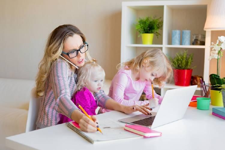 ama de casa toma notas en computador rodeada de hijos y hablando por teléfono