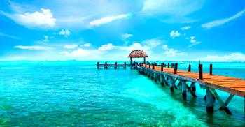Cielo azul con pocas nubes, muelle de madera con con una choza al final, sobre un mar de aguas cristalinas y color turquesa