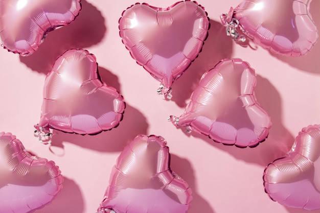 globos-aire-forma-corazon-sobre-fondo-rosa-luz-natural-bandera-amor-boda-zona-fotos-vista-plana-vista-superior_164357-14