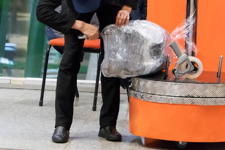 trabajador del aeropuerto envuelve en plastico una maleta