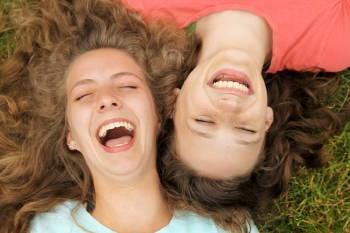 dos amigas se ríen a carcajadas sobre el pasto