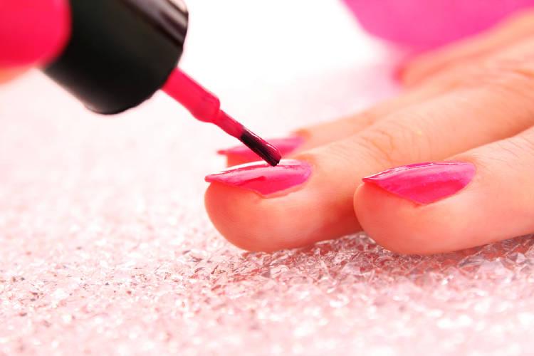 Una mujer se pinta las uñas con esmalte rojo