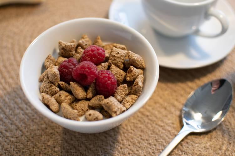 Cereales en un recepiente junto a una taza de café