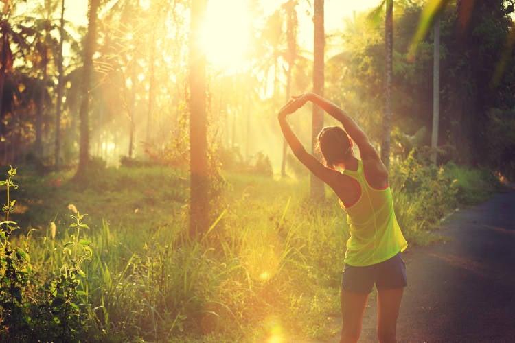 mujer entrena al amanecer en la naturaleza