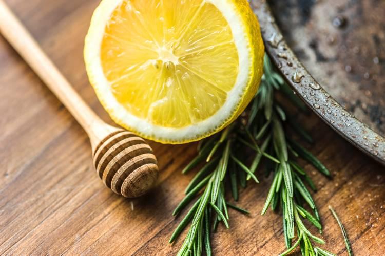 Ramas de tomillo junto a medio limón y una cuchara para miel