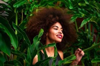 Una mujer con un afro entre hojas de plantas