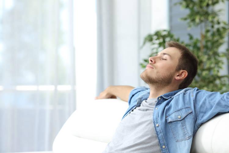 hombre se relaja en un sillon blanco