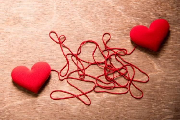 Dos corazones unidos por un hilo rojo