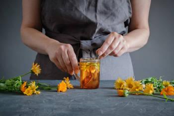 mujer prepara medicina herbal con flores