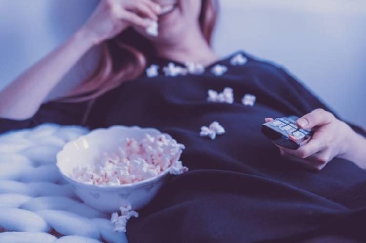 Una mujer mira televisión en la cama y come palomitas