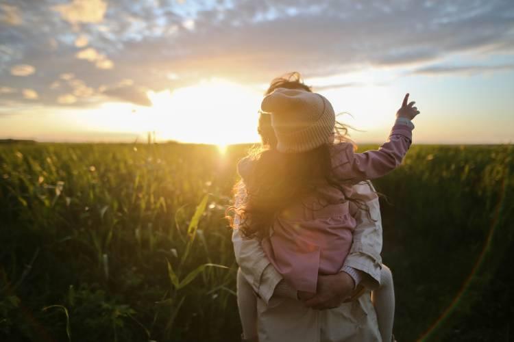 Una mujer con su hija en un campo al atardecer
