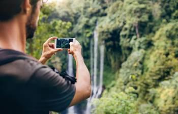 Un hombre toma una foto de una cascada