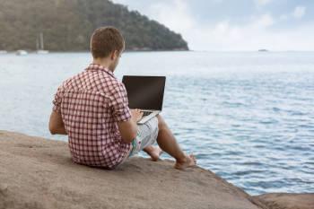 nomada digital trabaja en la playa desde su computadora
