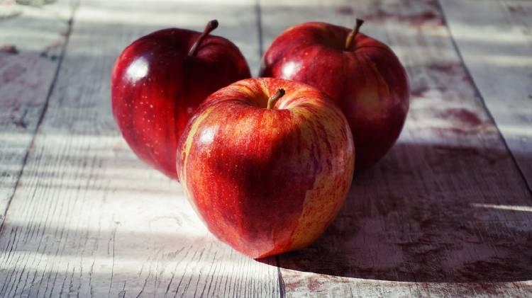Tres manzanas rojas sobre una mesa