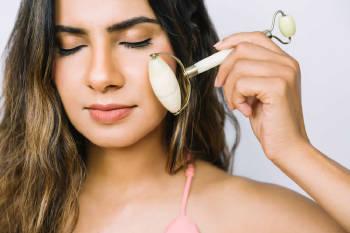 mujer se realiza masajes faciales con un rodillo de jade