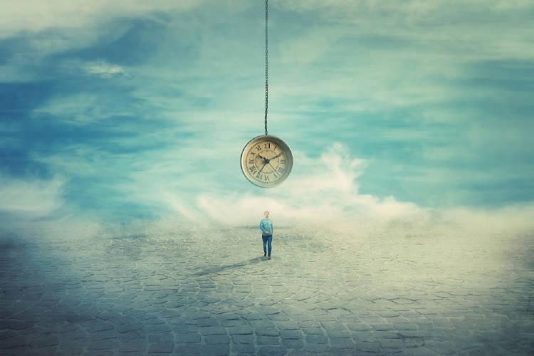 Un hombre parado en un lugar solitario con un reloj que cuelga sobre su cabeza