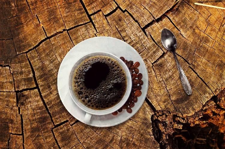taza de café con con granos de café a un lado